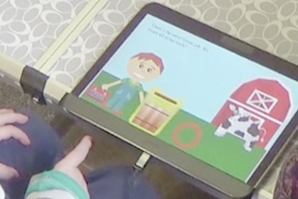 close up of child playing learning game on tablet