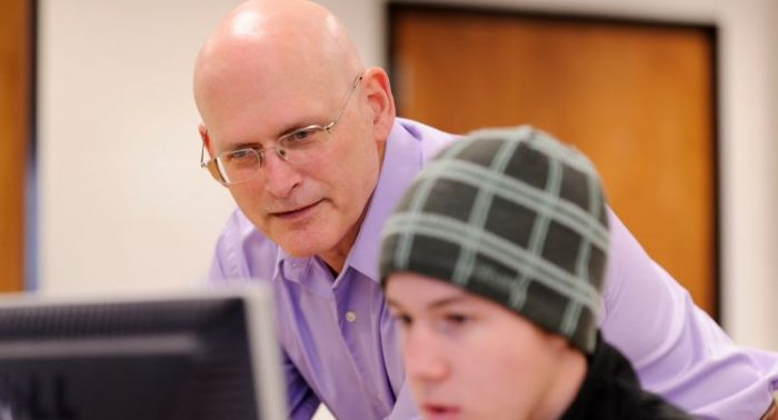 Steve Ackerman looking at a computer screen with a student
