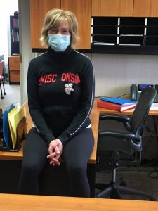 Peggy Ziebarth at her desk in Bascom Hall wearing a face covering.