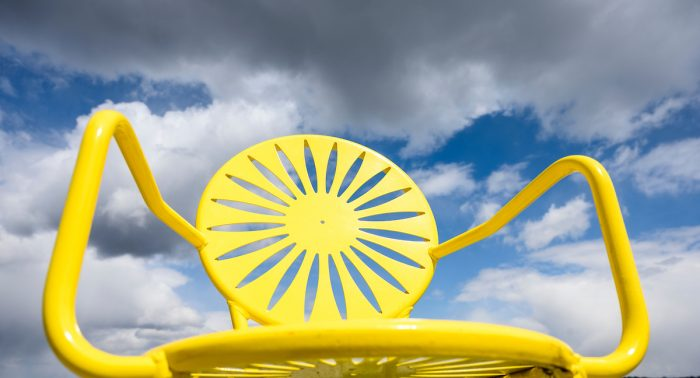 The yellow color of a sunlit Memorial Union Terrace chair stands in contrast to a partly cloudy sky at the University of Wisconsin-Madison during spring on April 21, 2021. (Photo by Jeff Miller / UW-Madison)
