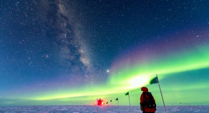"""A """"winterover"""" — one of the two staff members who stay through the minus-100-degree Fahrenheit nights of Antarctica's coldest months — hikes underneath the stars and aurora to the South Pole home of IceCube, a UW–Madison-led neutrino telescope frozen in a cubic kilometer of ice. Yuya Makino, assistant scientist, IceCube Neutrino Observatory"""